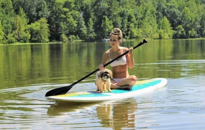 Girl paddle boarding on lake with dog.